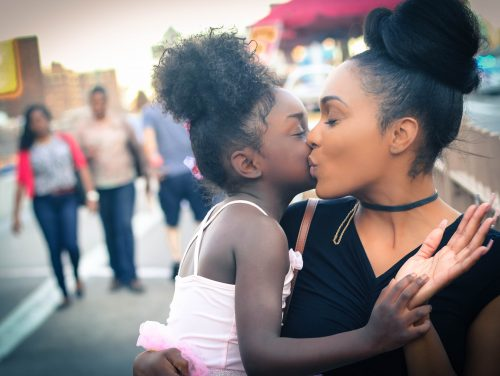 Mum kissing daughter