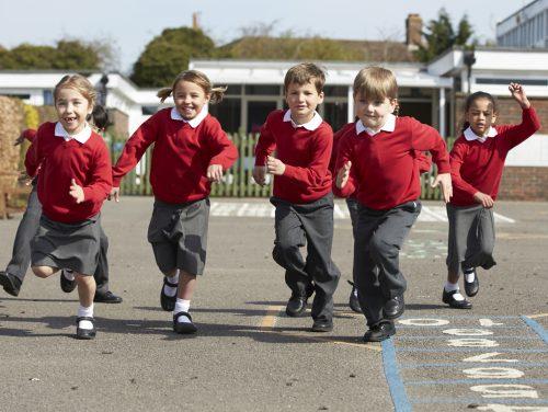 Elementary School Pupils Running In Playground